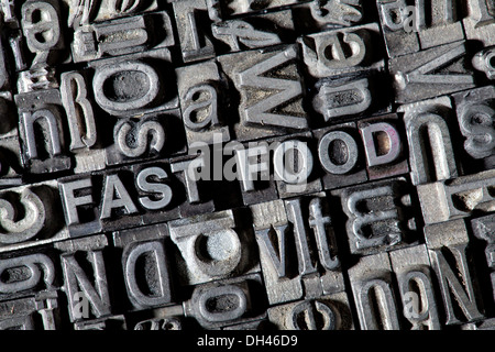 Old lead letters forming the term FAST FOOD - Stock Photo