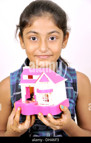 Indian Girl Holding Toy House piggy bank   MR#682W - Stock Photo