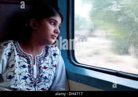 Girl listening to music and looking out of train window Jodhpur Rajasthan India Asia   MR#704 - Stock Photo