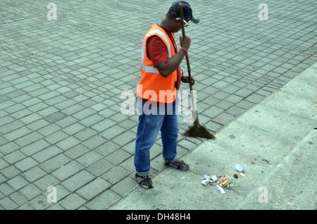 Man sweeping cleaning footpath Marine Drive Mumbai Maharashtra India - Stock Photo
