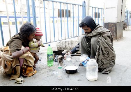 family living cooking man preparing milk powder for child on footpath pavement kolkata West Bengal India - Stock Photo