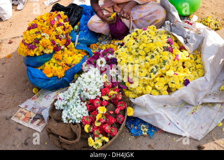 Indian women selling flowers for celebratory religious garlands at market. Andhra Pradesh, India - Stock Photo