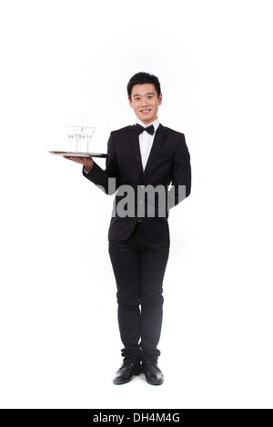 Man in tuxedo holding a plate - Stock Photo