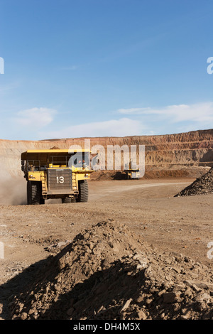 Gold mine operation in open cast surface pit with large haul truck leaving and excavators working behind, Mauritania, - Stock Photo