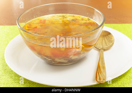 transparent lentil soup in a glass dish - Stock Photo