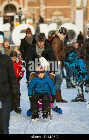 Netherlands, Amsterdam, Children getting used to iceskating on frozen pond in front of Rijksmuseum. - Stock Photo