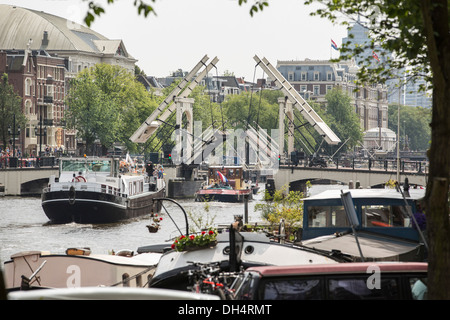 Netherlands, Amsterdam, Boats passing opened drawbridge Skinny Bridge. In front  houseboats. Back Carre theater, - Stock Photo