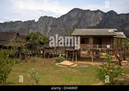 Horizontal view of typical stilted wooden houses along a countryside street in Laos. - Stock Photo