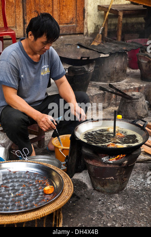 Vertical portrait of a Lao man deep frying small doughnuts in a wok on the roadside. - Stock Photo
