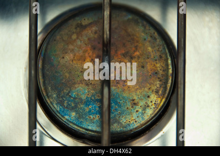 Horizontal close up of the colours on the top of a gas stove. - Stock Photo