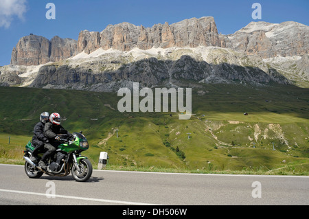 Motorcyclists in front of the Sella massif on the Pordoi pass, South Tyrol, Italy, Europe - Stock Photo