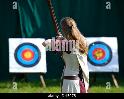 Woman wearing medieval clothes practising archery, Spectaculum, Maxlrain, Bavaria - Stock Photo