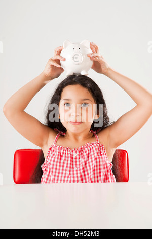 Girl holding a piggy bank on her head - Stock Photo
