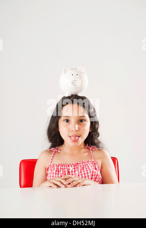 Girl with a piggy bank on her head - Stock Photo