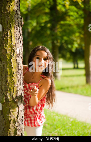 Smiling girl looking out from behind a tree - Stock Photo