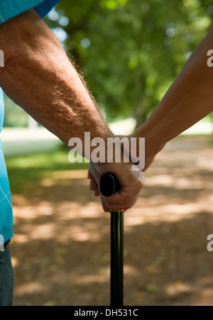 Woman putting her hand on the hand of an elderly man holding a walking stick - Stock Photo