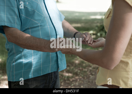A Woman and an elderly man holding each other hands - Stock Photo