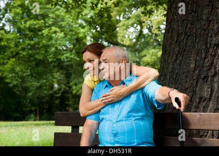Woman hugging an elderly man on a bench in a park - Stock Photo