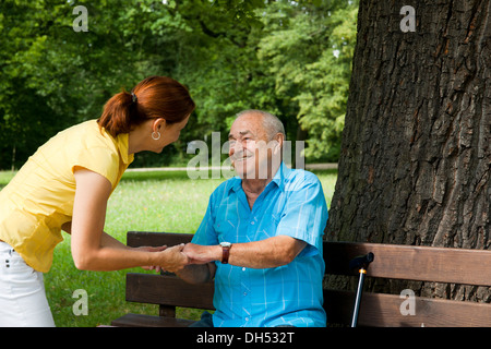 Women looking after an elderly man sitting on a bench in a park - Stock Photo