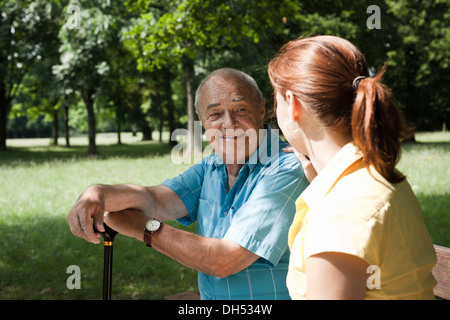 A women and an elderly man having a chat in a park - Stock Photo