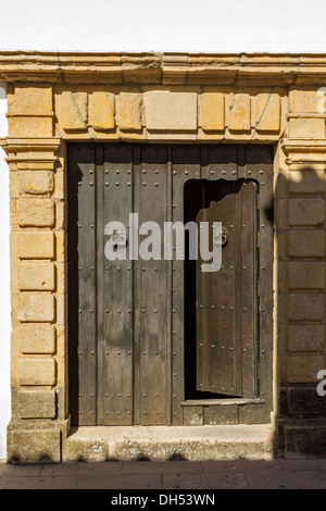 OLD WOODEN DOORWAY WITH OPENING IN RONDA ANDALUCIA SPAIN - Stock Photo
