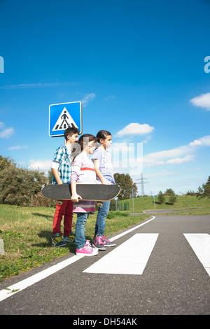 Children crossing a zebra crossing - Stock Photo