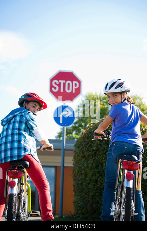 Boy and girl waiting with their bicycles in front of a stop sign - Stock Photo