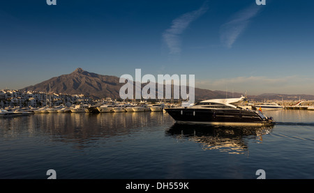 PUERTO BANUS COSTA DEL SOL IN THE EVENING WITH A BLACK BOAT ENTERING THE HARBOUR - Stock Photo