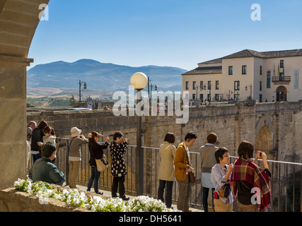 TOURISTS ON THE BRIDGE OVER THE EL TAJO CANYON OR GORGE IN RONDA ANDALUCIA SPAIN - Stock Photo