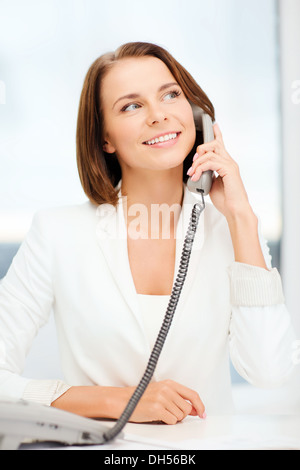 businesswoman with phone in office - Stock Photo