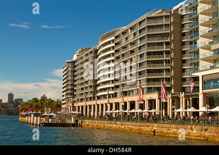 High rise waterfront apartment blocks beside blue waters of Darling Harbour in Sydney NSW Australia - Stock Photo