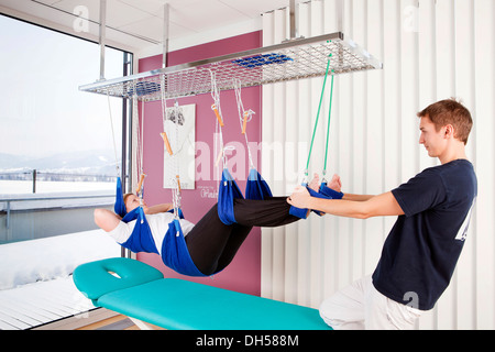 Patient and physiotherapist during sling table therapy - Stock Photo