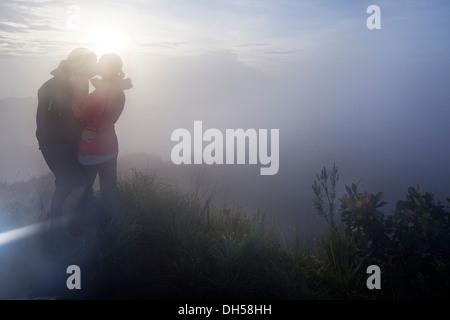 Couple kissing in the fog on the Gunung Agung volcano, Bangli, Bali, Indonesia - Stock Photo
