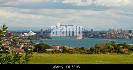 Panoramic city landscape showing Sydney harbour bridge, iconic opera house, and houses beside blue waters of Darling - Stock Photo