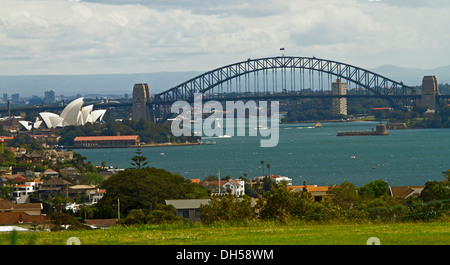 City landscape showing Sydney harbour bridge, iconic opera house, and houses beside blue waters of Darling Harbour - Stock Photo