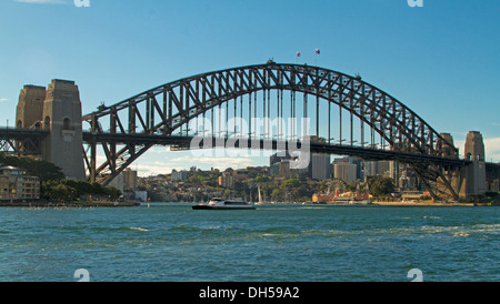 Panoramic view of Sydney harbour bridge spanning blue waters with commuter ferry passing beneath this iconic structure - Stock Photo