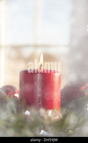 Dreamy image of a Red Christmas candle burning inside a wreath, with a window on background - Stock Photo