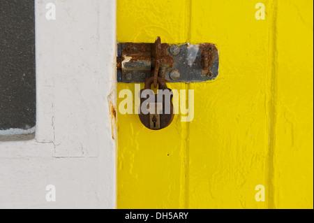 Rusty lock and padlock on a bright yellow door - Stock Photo