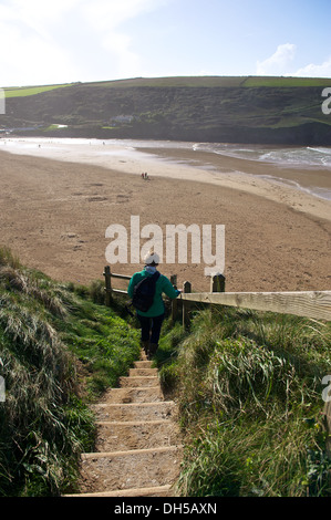 Woman walks down a path to Mawgan Porth beach in Cornwall England