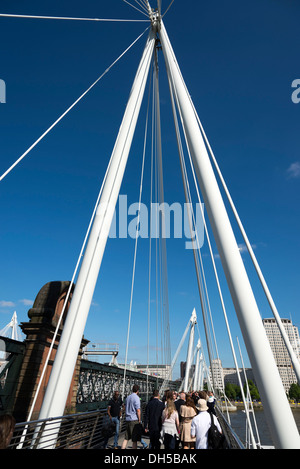 People crossing the river Thames on one of the Golden Jubilee Bridges , London, England, UK - Stock Photo