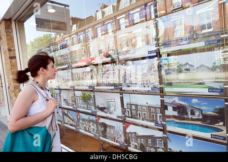 Young woman looking at houses for sale in estate agent window, Islington, London, England, UK - Stock Photo
