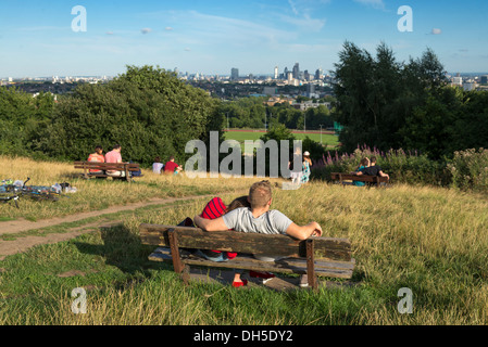 Young couple enjoying the view from a bench on Parliament Hill, Hampstead Heath, London, England, UK - Stock Photo
