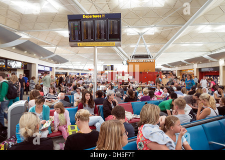 People waiting in the crowded departures lounge of Stansted airport, England, UK - Stock Photo