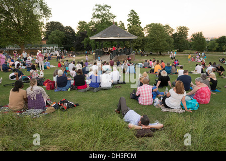 People listening to live music at the Parliament Hill bandstand in Hampstead Heath on a summer evening, London, - Stock Photo