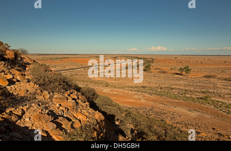 Vast barren Australian outback landscape with road slicing across treeless plains stretching to distant horizon - Stock Photo