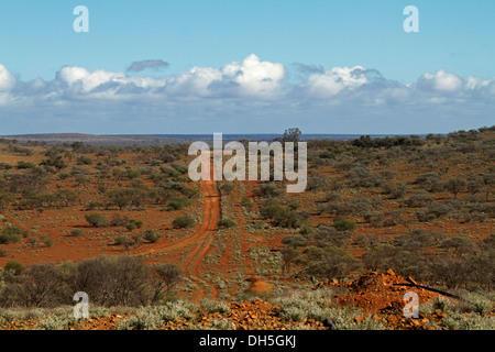 View of vast outback landscape with red road leading across plains with low vegetation from hill to distant horizon - Stock Photo