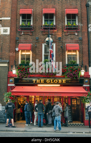 People drinking outside The Globe pub, Bow Street, London, England, UK - Stock Photo