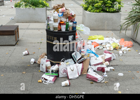 Takeaway bags and drinks containers overflowing from litter bin, London, England, UK - Stock Photo