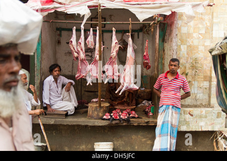 Roadside slaughterhouse, skinned animals hanging from beams, raw meat underneath, butcher waiting for customers, - Stock Photo