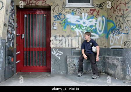 Weary boy, 10 years, sitting in a doorway, Cologne, North Rhine-Westphalia - Stock Photo